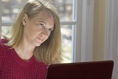 Blondes weibliches Sitzen am Computer-Denken Stockbilder