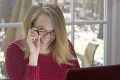 Blondes weibliches Sitzen am Computer mit den Händen auf Augen-Gläsern Lizenzfreie Stockfotos