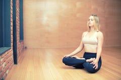 Blondes weibliches Sitzen in einem Lotussitz in einem Yogastudio Stockfotos