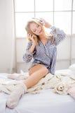 Blondes weibliches Sitzen im Bett und Hören Musik Lizenzfreie Stockbilder