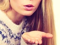 Blondes womn, das Luftkuß auf Palmenhand sendet Lizenzfreies Stockbild