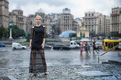 Blondes wooman dreesed im schwarzen Kleid in der Stadt Regnerischer Tag Stockbild