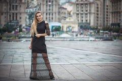 Blondes wooman dreesed im schwarzen Kleid in der Stadt Regnerischer Tag Lizenzfreie Stockfotos