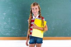 Blondes Zopfschulmädchen mit gewundenem Notizbuch des Studenten Stockfotografie