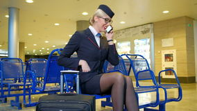 Blondestewardess die op telefoon in vertrekzaal babbelen stock footage