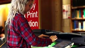 Blondestudent die het fotokopieerapparaat in de bibliotheek met behulp van stock footage