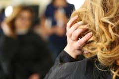 Blondevrouw bij kapper die haar kapsel controleren royalty-vrije stock foto