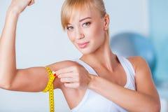 Blondevrouw die bicepsen meten Stock Foto