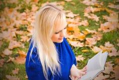 Blondevrouw die een boek in het de herfstpark lezen stock afbeelding