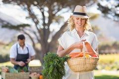 Blondevrouw die een groentenmand houden stock foto