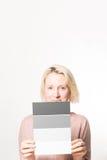 Blondevrouw die een vier-Stap Gray Scale Card Copy Space houden stock foto