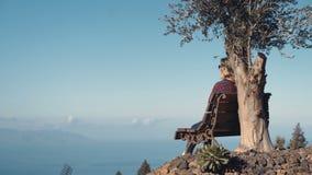 Blondevrouw die en onder een olijfboom bovenop een vulkanisch eiland in de Atlantische Oceaan rusten ontspannen stock footage