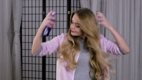 Blondevrouw die haar haar doen spritz hairspray stock footage