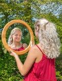 Blondevrouw die haar spiegelgedachtengang bekijken stock fotografie
