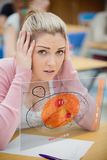 Blondevrouw die hard terwijl het bestuderen op futuristische interfac denken stock foto