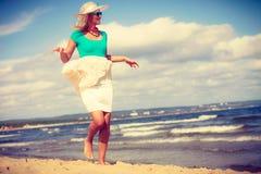 Blondevrouw die kleding dragen die op strand lopen royalty-vrije stock afbeeldingen