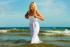 Blondevrouw die kleding dragen die in water lopen stock foto's