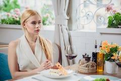 Blondevrouw die lunch hebben bij restautant stock afbeeldingen