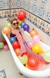 Blondevrouw die met zonnebril in haar badbuis spelen met heldere gekleurde ballons Sensueel meisje met witte rode gestreepte kous Royalty-vrije Stock Afbeeldingen