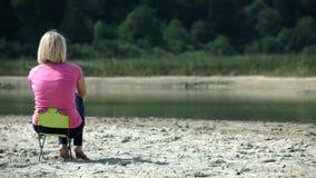 Blondevrouw die op een kleine stoel naast een rivier rusten stock video