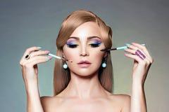 Blondevrouw die Samenstelling toepassen Kleurrijke Make-up stock fotografie