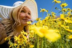 Blondevrouw die stro witte hoed draagt die een gebied van gele wildflowers ruikt Concept voor de hulp van de de lenteallergie stock fotografie