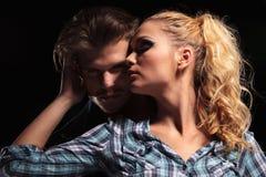 Blondevrouw die weg en haar vriend omhelzen kijken Stock Foto