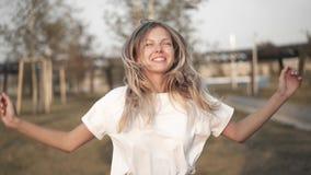 Blondevrouw die in witte t-shirt op trampoline buiten springen stock footage