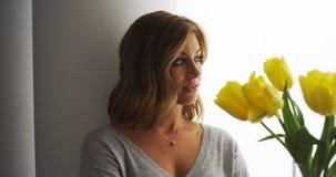 Blondevrouw die zich door een venster met een boeket van tulpen bevinden royalty-vrije stock foto's