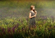 Blondevrouw die zich onder wildflowers bevinden Royalty-vrije Stock Afbeelding