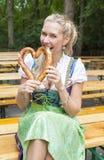 Blondevrouw in dirndl met pretzel Royalty-vrije Stock Afbeelding