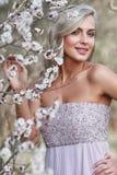 Blondevrouw in een gebloeide tuin royalty-vrije stock fotografie