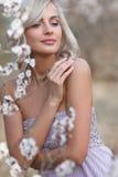 Blondevrouw in een gebloeide tuin royalty-vrije stock foto