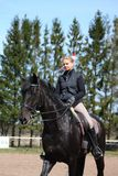 Blondevrouw en zwart paard Royalty-vrije Stock Afbeeldingen