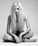Blondevrouw in haveloos jeans en vest royalty-vrije stock afbeelding