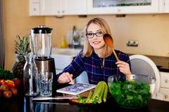 Blondevrouw het koken in keuken Lezingsrecept van tablet royalty-vrije stock afbeeldingen