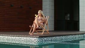 Blondevrouw het ontspannen dichtbij zwembad met mobiel Het sexy model mobiel typen stock video