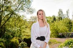 Blondevrouw in het oude zonnige park van de de zomerstad Jong vrouwen modern portret stock foto's