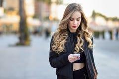 Blondevrouw het texting met haar smartphone op stedelijke achtergrond royalty-vrije stock afbeeldingen