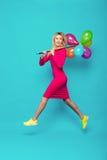 Blondevrouw met ballons op blauw stock foto