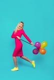 Blondevrouw met ballons op blauw royalty-vrije stock foto