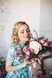 Blondevrouw met bloemen in licht minimalistisch binnenland Royalty-vrije Stock Fotografie