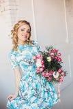Blondevrouw met bloemen in licht minimalistisch binnenland Royalty-vrije Stock Afbeeldingen