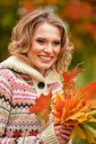 Blondevrouw met de herfstbladeren Royalty-vrije Stock Afbeeldingen