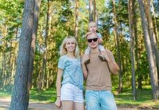 Blondevrouw met echtgenoot het stellen in het stadspark, familieportret stock afbeeldingen