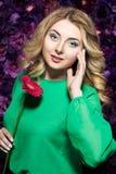 Blondevrouw met een zachte samenstelling die de camera terwijl het houden van bloem dichtbij het gezicht op een bloemenachtergron Stock Foto's