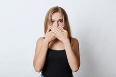 Blondevrouw met glanzende ogen, die haar mond behandelen met handen terwijl het proberen om stilte en het vertellen niet geheim v stock foto's