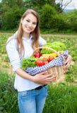 Blondevrouw met groenten vers van het gebied stock fotografie