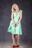 Blondevrouw met haar in de wind sexy meisje met het vliegen haar het stellen in groene kleding en rode schoenen stock foto's