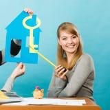 Blondevrouw met huis en sleutel Stock Afbeeldingen